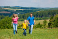 Family playing tag on meadow in summer Royalty Free Stock Images