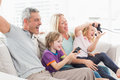 Family playing video game while sitting on sofa Royalty Free Stock Photo