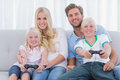 Family playing video games at home on the couch Stock Photo