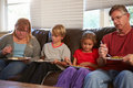 Family with poor diet sitting on sofa eating meal at home plates Stock Photo