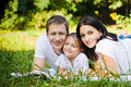 Family portrait in a park lie at meadow Royalty Free Stock Photos