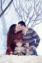 Family portrait sits on studio snow forest background Royalty Free Stock Photo