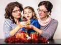 Family preparing gifts for christmas little girl and two adult women with present boxes and decorations Royalty Free Stock Image
