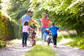 Family pushing bikes along country track in daylight looking at each other smiling Stock Image