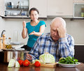 Family quarrel mature woman having conflict with husband women at kitchen Royalty Free Stock Photo