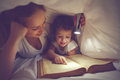 Family reading bedtime mom and child reading book with a flashl daughter flashlight under the blanket in bed Royalty Free Stock Photography