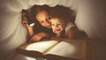 Family reading bedtime. Mom and child reading book with a flashlight under blanket Royalty Free Stock Photo
