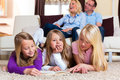 Family reading a book together at home in their living room Royalty Free Stock Photo