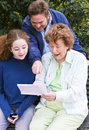 Family reading letter together grandmother her grown son and teenage granddaughter a Stock Photos