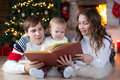 Family reading together on Christmas evening Royalty Free Stock Photo