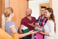 Family receiving visitors couple with a gifts in the home Royalty Free Stock Images