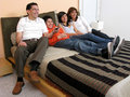 Family reclining in bed Royalty Free Stock Photos