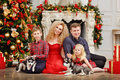 Family in red along with husky puppies sitting on Christmas back Royalty Free Stock Photo
