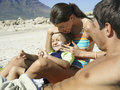 Family relaxing on beach boy sitting in mother s lap woman applying suncream to son s face side view women Stock Images