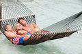 Family relaxing in beach hammock asleep Stock Photo