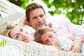 Family relaxing in beach hammock with sleeping daughter smiling to camera Royalty Free Stock Photography