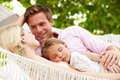 Family relaxing in beach hammock with sleeping daughter smiling to each other Stock Images