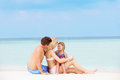 Family relaxing on beautiful beach together smiling Stock Photography