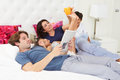 Family relaxing in bed with coffee and newspaper smiling Stock Photography