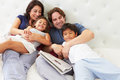Family relaxing in bed with coffee and newspaper smiling Stock Photo