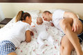 Family resting on a bed of roses young parents relaxing with baby boy in with clothing Royalty Free Stock Photo