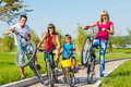 Family riding bicycles laughing kids and their parent with Stock Photo