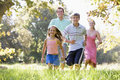 Family running outdoors smiling Royalty Free Stock Photos
