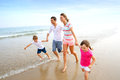 Family running on a sandy beach happy the Royalty Free Stock Photo