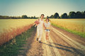 Family Running Together Through Summer Harvested Field. Happy family enjoying and running together outdoors. Royalty Free Stock Photo