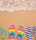 Family s flip flop pairs on sea surf with copy space for your text Stock Photos