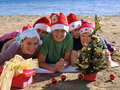 Family with Santa Claus hat on beach Stock Photos