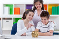 Family saving money mother with her children putting in piggybank Stock Photo