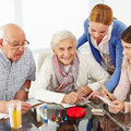 Family with senior couple playing happy parlor games Royalty Free Stock Photo