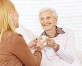Family with senior woman drinking women coffee in a retirement home Stock Images