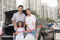 Family with shopping cart standing next to the car Royalty Free Stock Image