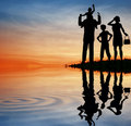 Family silhouette on sunset sky. Stock Photo