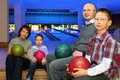 Family sit in club and hold balls for bowling Royalty Free Stock Image