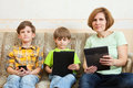 The family sit with gadgets on sofa electronic devices Royalty Free Stock Photos