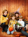 The family sit with halloween s carved pumpkin against wooden wall Royalty Free Stock Photography