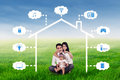 Family sits at field under smart house design Royalty Free Stock Photo