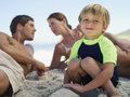 Family sitting on beach focus on boy crouching in foreground smiling portrait Royalty Free Stock Images