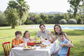 Family sitting at breakfast table in garden portrait of a smiling couple with three children the Royalty Free Stock Photo