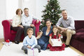 Family sitting by christmas tree at home portrait of happy with presents and Stock Photography