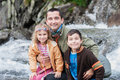 Family sitting close to mountain stream on trail and rocks in background Royalty Free Stock Image