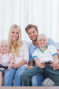 Family sitting on couch playing video games in the living room Stock Photos