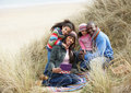 Family Sitting In Dunes Enjoying Picnic On Winter Stock Photography
