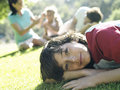 Family sitting on grass in park focus on boy in foreground portrait surface level tilt Stock Photography