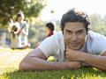 Family sitting on grass in park focus on man in foreground smiling portrait surface level men Stock Photos