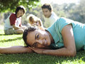 Family sitting on grass in park focus on woman in foreground smiling portrait surface level women Royalty Free Stock Photos