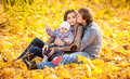 Family sitting on leaves at autumn park young Royalty Free Stock Images